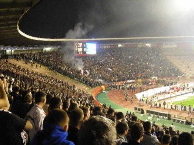 Fani Partizana chronią ogień przy pomocy flagi